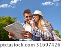 Cheerful young couple on a sunny day reading map 31697426