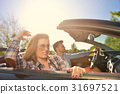 Couple of lovers driving on a convertible car - 31697521