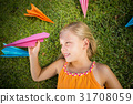 Young girl lying on grass around paper planes 31708059