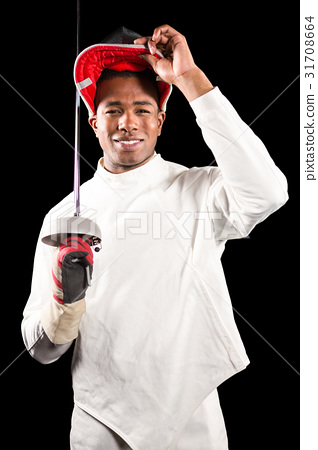Portrait of swordsman standing with fencing mask and sword 31708664