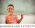 Portrait of smiling schoolboy playing flute in classroom 31710174