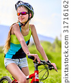 Woman traveling bicycle in summer park. 31716162