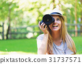 Female photographer with a camera outside 31737571