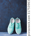 Pair of green woman canvas sneakers on blue 31750963