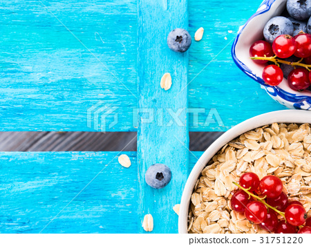 Rolled Oats and berries blue textured background 31751220