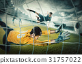 Goalkeeper in gates jumping to catching ball 31757022
