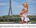 beautiful young blond woman with braid over city bridge. The fee 31779250