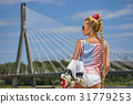 beautiful young blond woman with braid over city bridge. The fee 31779253