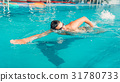 Swimmer in glasses swims in indoor swimming pool 31780733