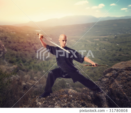 Wushu master with sword, meditation on mountain 31780808