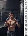 The young man workout a kick on the punching bag 31780867