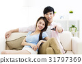 smiling  young couple watching tv  in living room 31797369