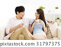 Portrait of  smiling  young couple sitting on sofa 31797375