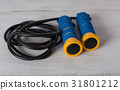 Blue and yellow skipping rope on white wood 31801212