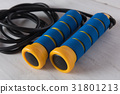 Blue and yellow skipping rope on white wooden back 31801213