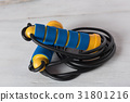 Blue and yellow skipping rope on  wood background 31801216