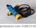 Blue and yellow skipping rope on wood 31801218