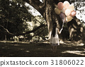 The girl stands alone holding a balloon in a park 31806022