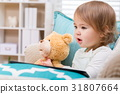 Happy toddler girl sitting with her teddy bear 31807664