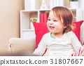 Toddler girl laughing in her living room 31807667