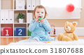 Toddler girl have tea with her teddy bear 31807688