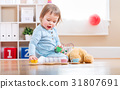 Toddler girl have tea with her teddy bear 31807691