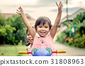 Child little girl raises her hand andride tricycle 31808963