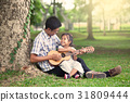 Father and child having fun play guitar together 31809444