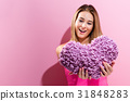 Happy young woman holding a heart cushion 31848283