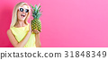 Happy young woman holding a pineapple 31848349