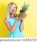 Happy young woman holding a pineapple 31848729