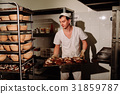 Handsome baker in uniform holding tray full of 31859787