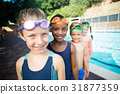 Smiling little swimmers standing at poolside 31877359