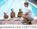 Female trainer teaching students at pool side 31877396