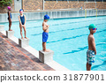 Swimmers standing on starting blocks at poolside 31877901
