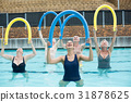 Happy trainer and senior swimmers exercising in swimming pool 31878625