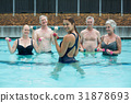 Strong female trainer with senior swimmers in swimming pool 31878693