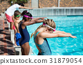 Swimmers with trainer ready to jump in pool 31879054