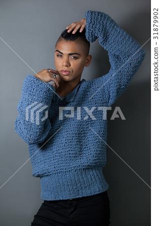 Portrait of confident transgender posing against gray background 31879902