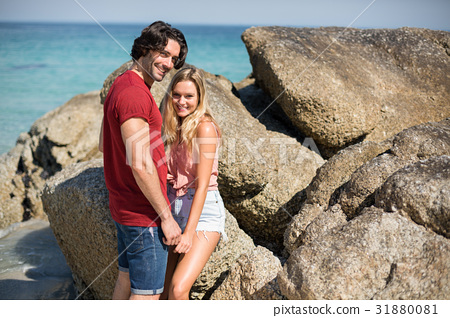 Portrait of romantic couple by rock formations at beach 31880081