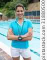 Portrait of smiling female coach standing with arms crossed 31880500