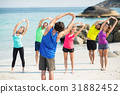 Friends in sportswear stretching while standing on shore 31882452