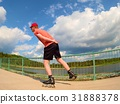 Rear view to inline skater skating on the bridge 31888378