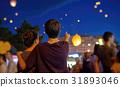 Teens watching paper flying lanterns 31893046