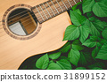 Acoustic guitar and green leaves background. 31899152