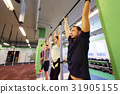 group of people hanging at horizontal bar in gym 31905155