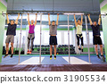 group of people hanging at horizontal bar in gym 31905534