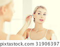 woman cleaning ear with cotton swab at bathroom 31906397