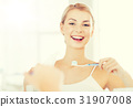 woman with toothbrush cleaning teeth at bathroom 31907008