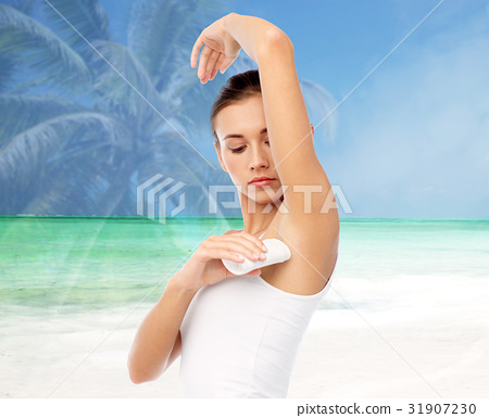 woman with antiperspirant deodorant over beach 31907230